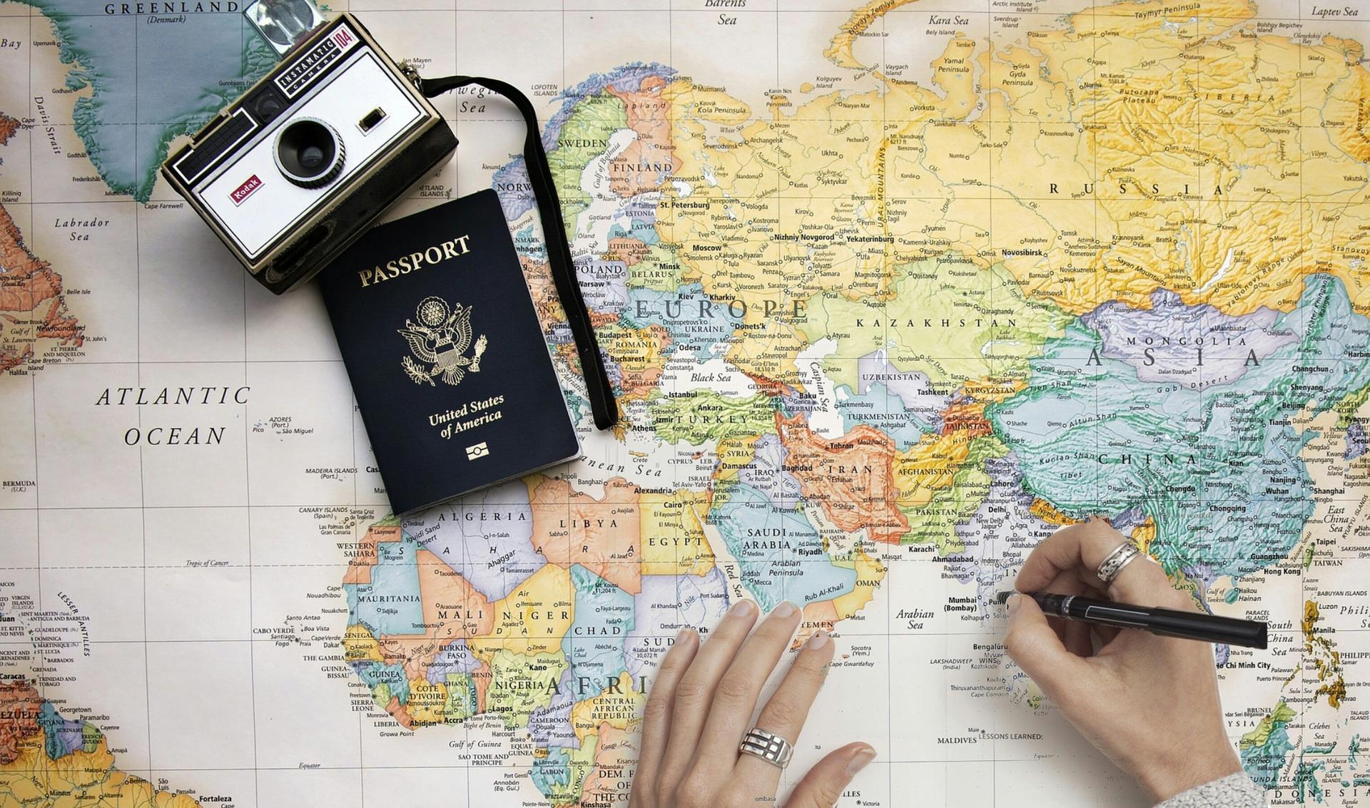 passeport et appareil photo posée sur une mappe monde