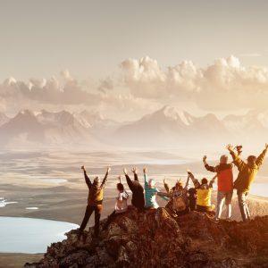 Groupe de jeune levant les bras devant un paysage en voyage surprise